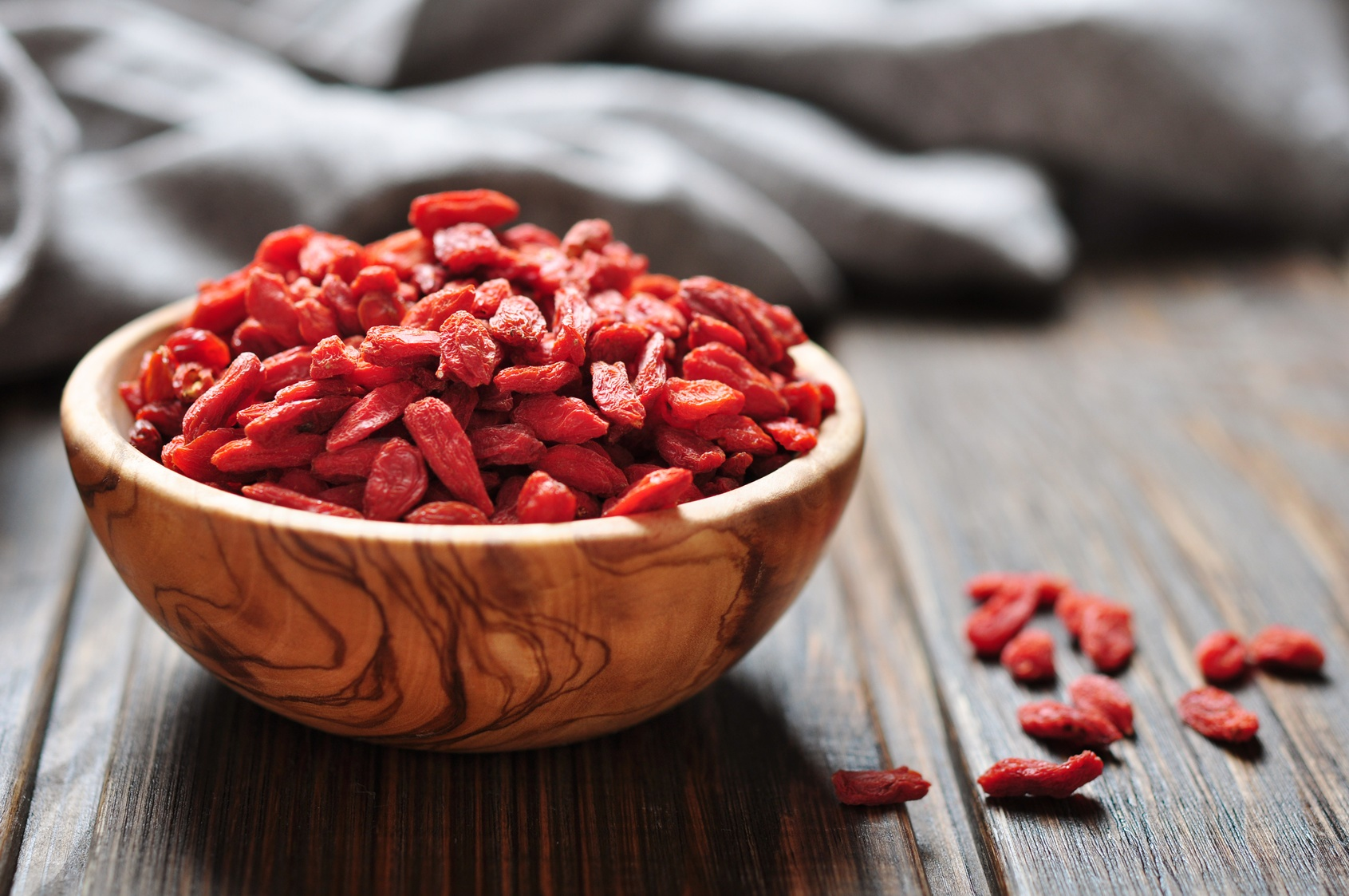 wooden bowl with goji berries on the table closeup